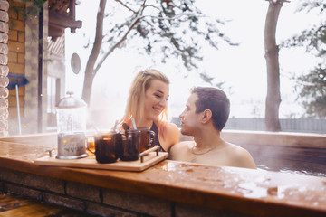 Couple drinking hot tea while sitting in the winter outside hot spa