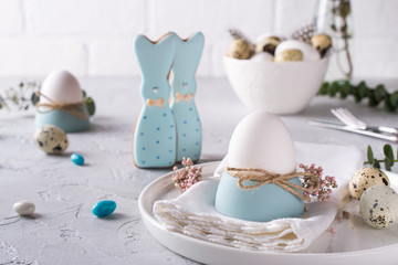 Homemade easter cookies in the shape of  a  funny  bunny, quail eggs  and chicken egg. Easter  celebration table setting. Holiday decorations.