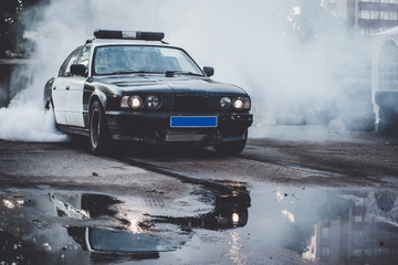 Police car on drift racing motorsport. German driftcar burning tires on asphalt in drift-show. Speed, drive and active sport