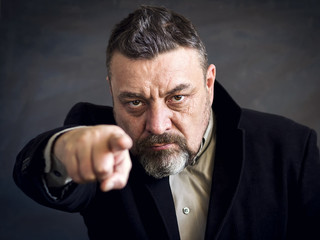 Angry bearded man in a black suit point a finger at you. Copy space. A gesture of choice.