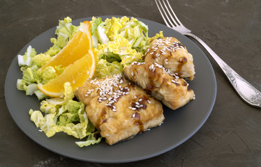 Fried fish with salad on a gray plate.
