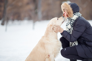 Photo of girl hugging labrador in snowy park