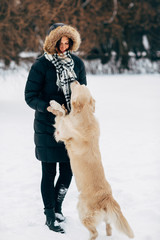 Image of woman in black jacket with retriever on walk in winter park