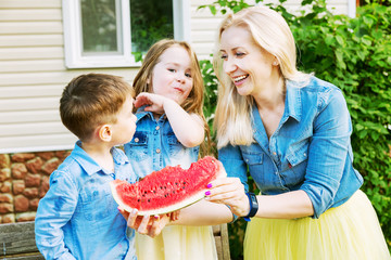 Young family eating watermelon in the yard of the house