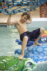 Young boy playing at the indoor water park