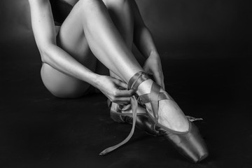 Beautiful legs of young ballerina who puts on pointe shoes  Ballet practice. Beautiful slim graceful feet of ballet dancer.