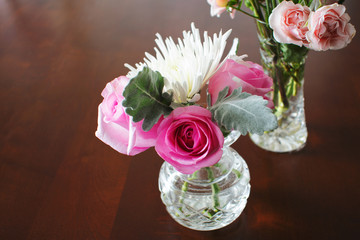 Two crystal vases with miniature flowers on wood table.
