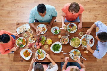 group of people eating at table with food