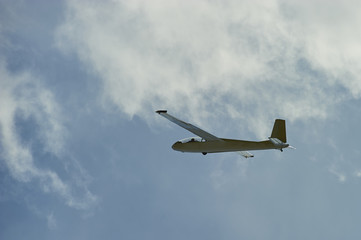 A Glider flying in blue sky with big white clouds. The glider is a plane that has no engine