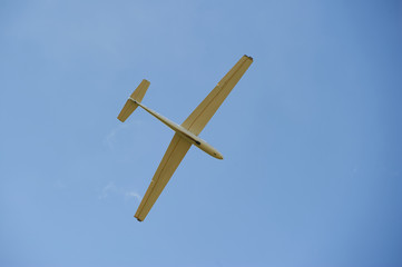 A Glider flying in bleu sky. The glider is a plane that has no engine