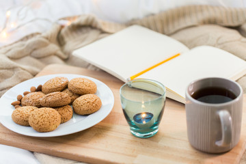 Fototapete - cookies, tea and candle in holder at home