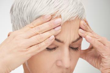 Head shot of senior woman having headache. Hands on head, eyes closed.