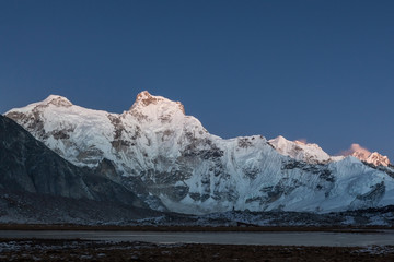Dusk lights over the mountain Cholatse summit in Himalayas, Nepal. Highlands scenery of the mountain range in pinkish dusk light. Beautiful background for your website header or banner.