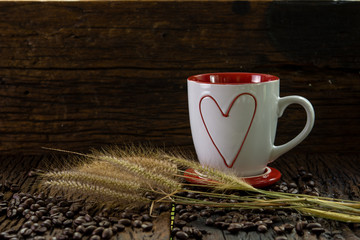 Red and white coffee cup with heart shape pattern, dry grass flowers and coffee beans on wood table and wooden wall
