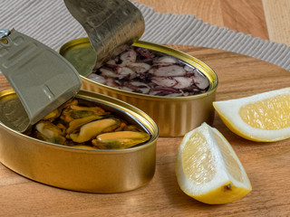Cans of preserves with mussels and octopus with lemon slices, set on a rustic wooden board