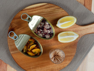 Cans of seafood preserves with mussels and octopus on a rustic wooden board, with lemon slices and toothpicks