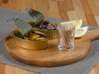 Cans of preserves with mussels and octopus on a rustic wooden board, with lemon slices and toothpicks