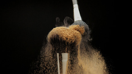 closeup of black brush with a facial powder on it and another brush whisk away a part of powder