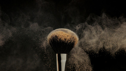 closeup of black brush with a facial powder on it and blowing out by wind