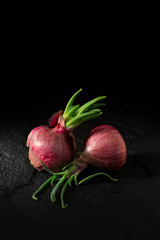 Shallots for cooking Put on the black rock in the dark background