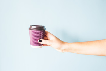 A woman with a black manicure holds in her hand a purple paper kraft disposable cup with coffee...