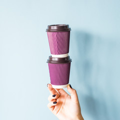 Purple paper kraft disposable cups for coffee with plastic lids in a female hand. One glass stands...
