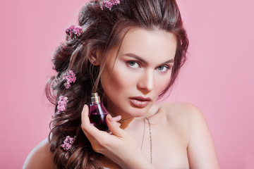 Close up studio portrait of young beautiful woman holding perfume in small flacon, posing on pink background. Model with nude makeup, greek braid hairstyle with flowers. Perfumery advertising concept
