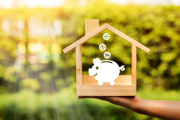 Woman hand holding a wooden home with piggy bank and dollar coin model made of paper art is placed inside on nature bokeh in the public park, Loan or save money for buy a house and real estate concept