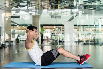 Full length side view of a fit young man sitting down on exercise mat, while doing full range crunches for the abdominal muscles at the gym