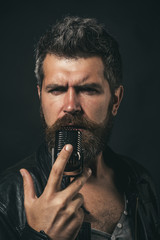 Emotional portrait attractive guy with beard. Male vocalist singing in microphone in recording studio. Life style concept - handsome man with beard wearing leather jacket holds microphone and singing.