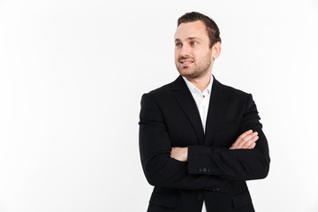 Portrait of young businessman looking aside while standing in suit with broad smile keeping arms folded, isolated over white background