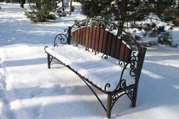 bench in the snow / a bench covered with snow in the winter noon