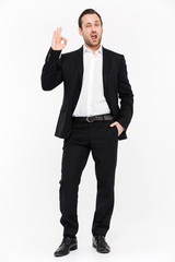 Full-length portrait of smiling entrepreneur having stubble wearing black suit and showing OK sign, isolated over white background