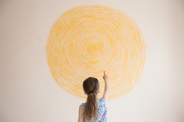 little girl points her finger at yellow sun painted on wall