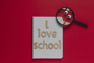 "Magnifying glass with eyes looking at ""I love school"" lettering on a notebook. Red background."