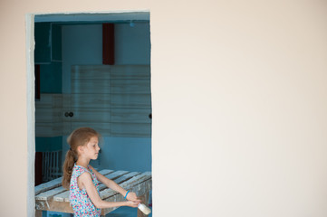 cute small girl in summer dress with a brush painting wall in new house with copy space