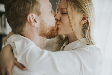 Loving couple kissing in the room