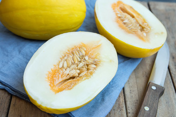 Ripe Organic Fresh Melon Whole and Cut in Half on Blue Napkin Knife on Plank Wood Garden Table. Summer Seasonal Fruits Harvest Vitamins Healthy Diet Concept