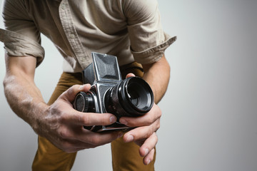 Fashion Photographer with an old film camera in hand while working in studio.