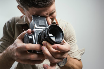 Fashion Photographer with an old film camera in hand while working in studio. .Closeup with focus on the camera.