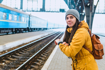 woman check time. waiting for train on railway station