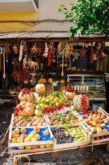 rustic Italian market with fresh fruits, boxes of grapes and oranges, hanging bunches of yellow and red grapes and bunches of chili peppers