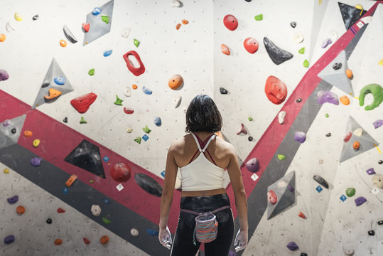 Unrecognizable woman ready for practice rock climbing on artificial wall indoors.