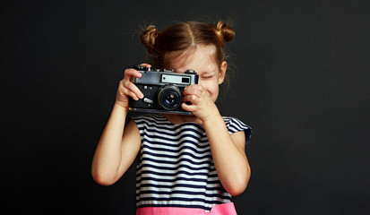 Portrait of cute stylish girl taking photo with old vintage camera.