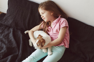 Portrait of little girl hugging with puppy of Jack Russell Terrier dog on the bad with black sheets