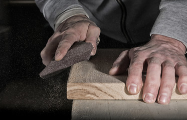 Detail of male hand using a sanding block to sand timber desk Wall mural