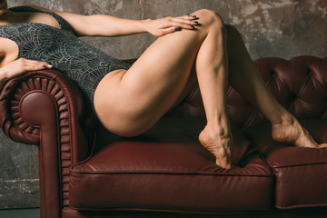 Resilient fit legs hips and buttocks. beautiful sporty sporty girl in luxurious swimsuit body posing on against sofa. Vertical composition. Body parts