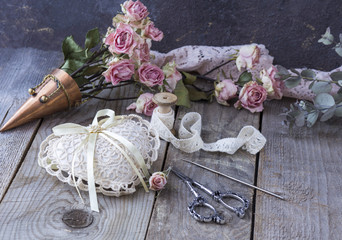 Handmade background. on a wooden table lace, scissors, hook for knitting, heart made of lace, roses