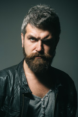 Gorgeous and stylish. Cool man in gray t-shirt and black leather jacket. Seasonal fashion. Serious handsome bearded man with stylish hairstyle.