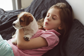Portrait of little girl hugging with puppy of Jack Russell Terrier dog on the bad with black sheets and giving kisses to a dog